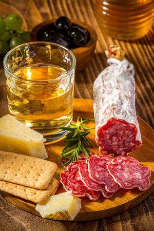 Sliced Salame on Wooden Plate with Cheese and Wine. Italian Appetizer.