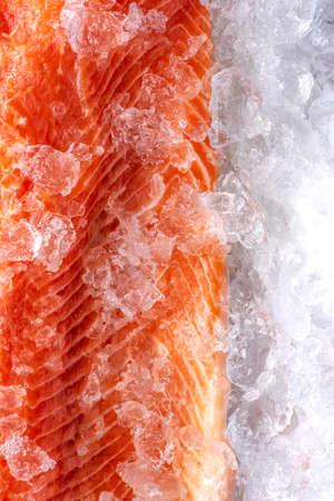 Salmon Piece Raw Meat on Ice. Food Background Closeup View. 免版税图像