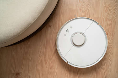 robot vacuum cleaner removes dust in room on brown floor. vacuum cleaner in ordinary apartment. modern household wireless device for cleaning house. smart home concept