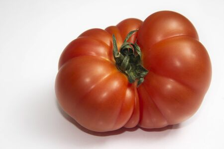 Macro red tomato isolated on a white background. Advertisement space. Horizontal view.