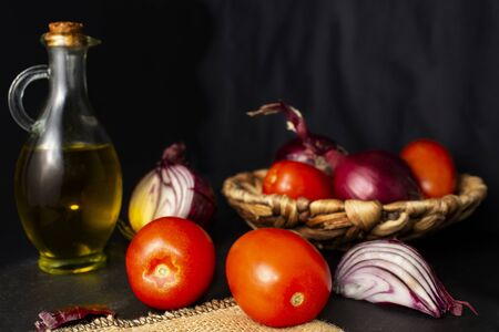 Colorful still life of fresh vegetables, ingredients of a salad or spanish gazpacho. Red tomatoes pear, purple onion and bottle of olive oil. Horizontal view. Black background.