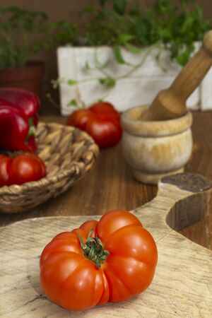 Still life of a tomato and ingredients for salad on a wooden kitchen table. Rustic atmosphere. Vertical view.