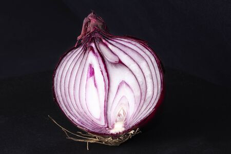 Close up of a half onion isolated in a black background. Advertisement space. Horizontal view. Color contrast.