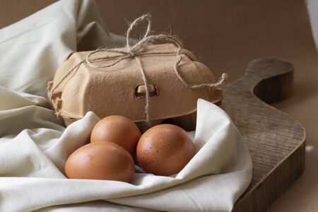 Delicate life style Delicate still life with three eggs and an egg carton packed with string on a kitchen board. Soft beige tones.Horizontal view.