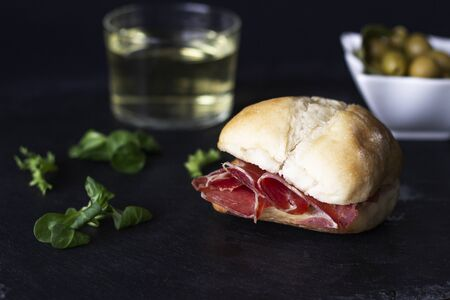 Close up appetizing muffin with serrano ham in low key with an appetizer background of olives and wine in the background slightly out of focus and a little green lettuce. Foto de archivo