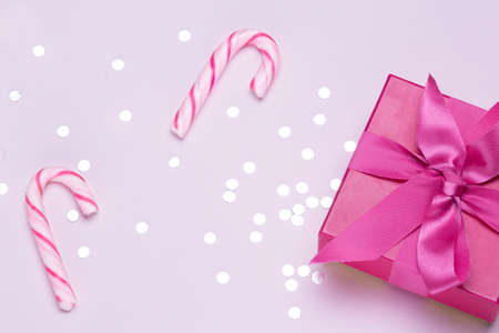 Pink gift with candy cane and silver confetti. Copy space for advertising. Concept to celebrate and to congratulate.