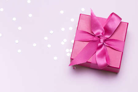 Pink gift with silver confetti. Copy space for advertising. Concept to celebrate and to congratulate. Imagens