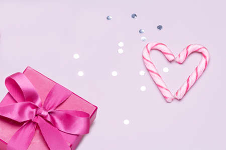 Pink gift with candy cane and silver confetti. Concept to love and friendship, celebrate and congratulate.Copy space for advertising. Imagens