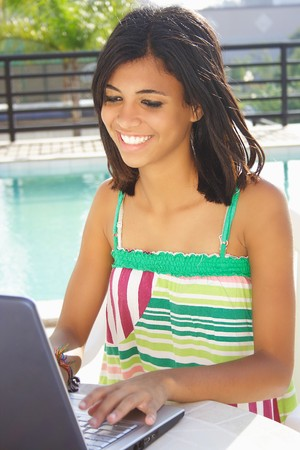 Teenager having fun with notebook next pool. photo