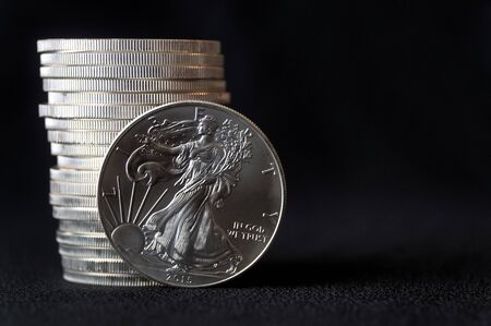 A shiny new American silver eagle coin in front of a stack of similar silver eagle coins