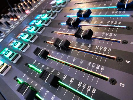 Angled perspective on volume faders on a digital soundboard for a church 写真素材
