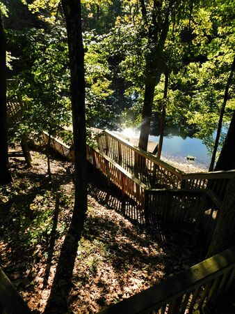 View looking down the stairs to the boat dock by the lake, with the morning sun reflecting off the water, at Blue Mountain Camp in Hamburg, Pennsylvania