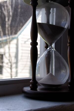 Large hour glass in a window to the right of frame