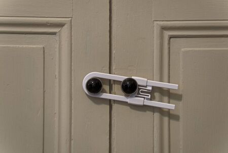Close up view of a white child safety lock holding two cabinet doors together