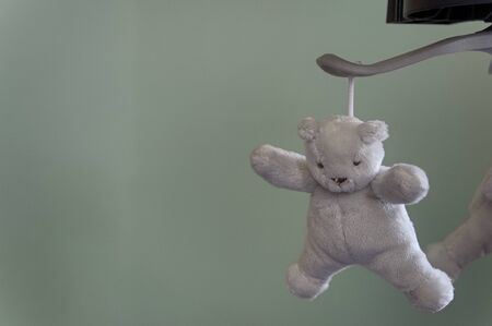 One grey, white plush teddy bear hanging from a mobile, with copy space to the left