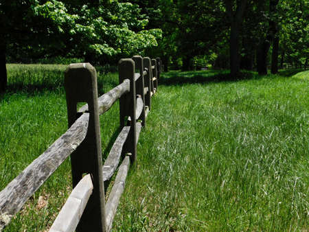 A wooden post fence runs through a grassy field in northern Delaware 免版税图像