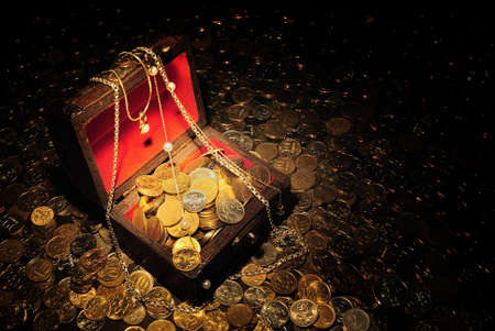 Scattering of coins around and inside trunk with treasure.