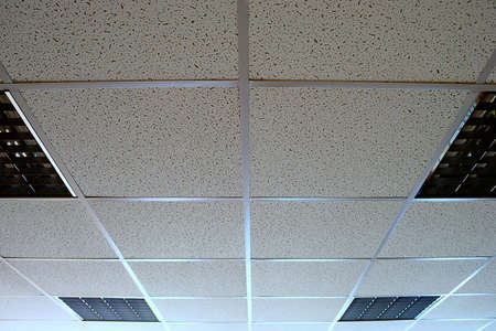 Office suspended ceiling with switched-off fluorescent lighting.