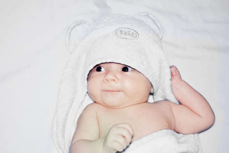 sympathetic: Cutie baby wrapped in a terry towel has a rest after bathing