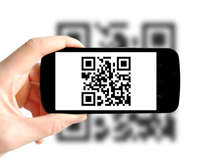 bars code:           hand holding a smartphone that is scanning a QR Code Stock Photo