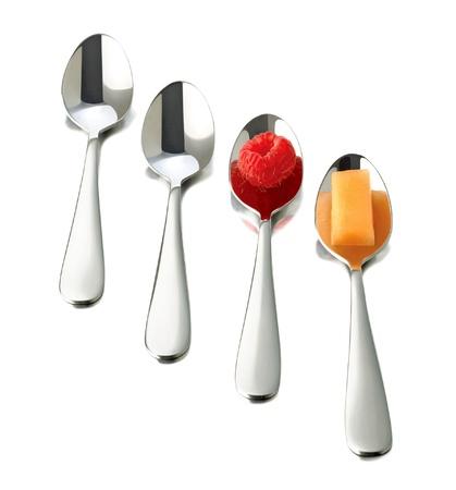 four spoons on white background. raspberry on spoon
