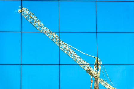 crane reflection over a building with blue sky