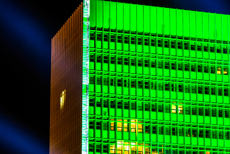 horizontal image of a building with green lights at night