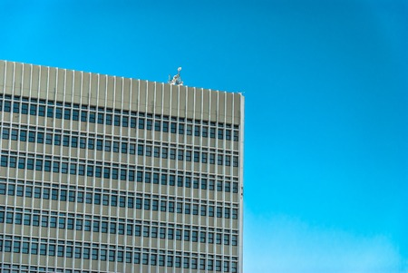 horizontal image of cement tall building with windows and the sky
