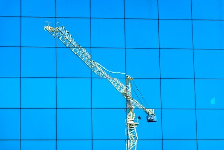 crane reflection over Window building in blue sky