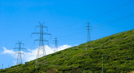 horizontal image of an electricity pylo on the mountain and the blue sky