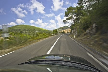 Car speeding on the road to mountains - holiday travel rush