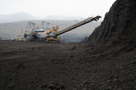 Mining of coal in the open pit mine with heavy machinery