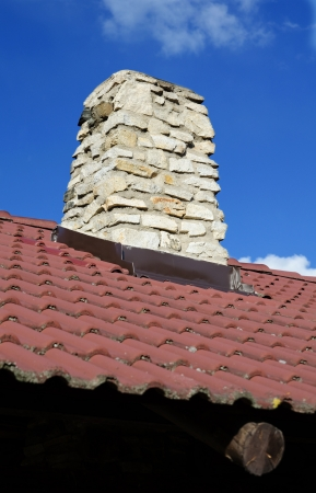 rooftiles: Classic chimeny made of stone on dark brown-red roof