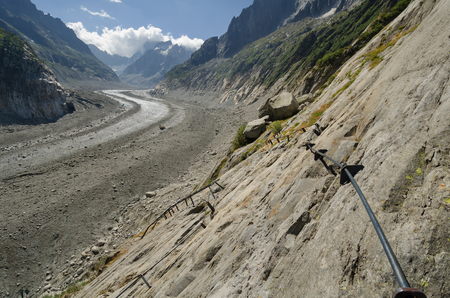 Mountain landscape in the French Alps with Mer-de-Glace glacier and climbing trail in the foreground Stock Photo