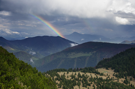 Hilly landscape with spruce forests, hiking trail and rainbow in Mala Fatra mountains, Slovakia, Europe