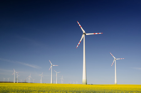 Landscape with yellow flowering rape field and group of wind turbines - clean energy production Stock Photo
