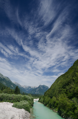 Valley with alpine river Soca, mountains and sky, Slovenia Stock Photo