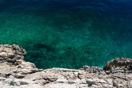 Limestone cliff and clear blue-green sea at the coast of Istria peninsula, Croatia