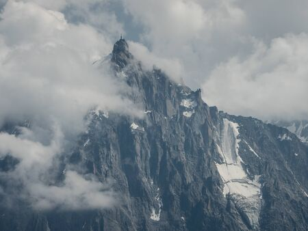 Alpine landscape with cloudy and snowy Aiguille du midi peak, French Alps, Chamonix, France