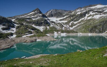 Alpine lake with snowy peaks above Enzingenboden, Hohe Tauern NP, Austria Standard-Bild