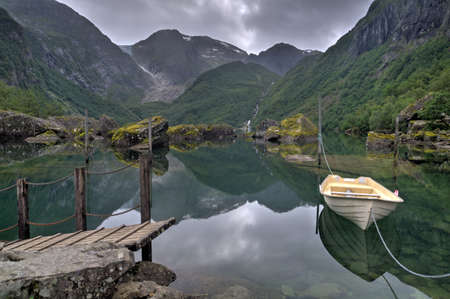 Summer landscape in overcast and rainy day with mountains, lake and a boat in Bondhusdalen valley, Norway, Scandinavia