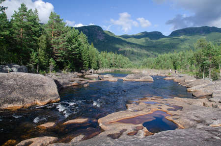 Clean wild river with rocky shore and deep forests, central Norway, Scandinavia
