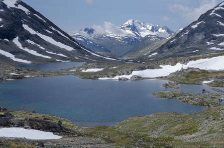 Summer landscape with snowy peaks and lakes of Jotunheimen mountains ridge, Norway, Scandinavia