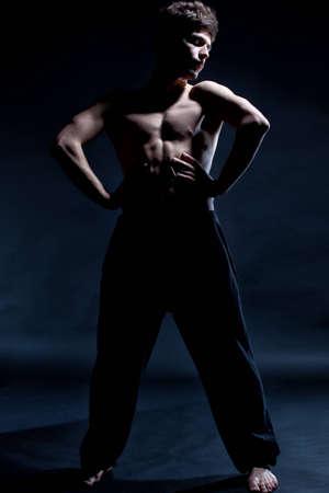 Modern ballet dancer posing over black background
