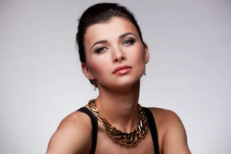 Portrait of luxury woman in exclusive jewelry on natural background photo