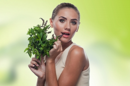 Close-up portrait of happy young woman with with a bundle of fresh mint  Concept vegetarian dieting - healthy food Stock Photo