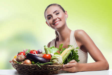 Happy young woman holding basket with vegetable  Concept vegetarian dieting - healthy food Фото со стока