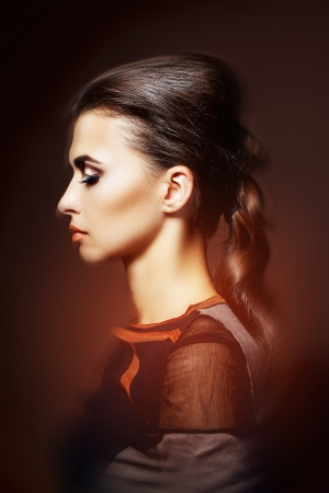Fashion studio shot of beautiful woman  with a luxurious hairstyle and professional makeup photo