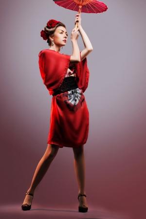 Fashion asian woman wearing traditional japanese red kimono  with umbrella, studio shot   Geisha