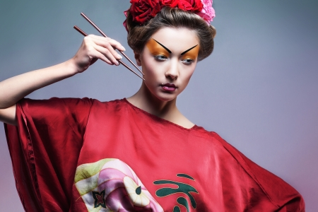 Fashion asian woman wearing traditional japanese red kimono  with umbrella, studio shot.  Geisha photo